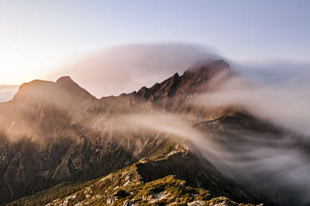 Mountain scenery with clouds and mist in the morning, the peak is famous Mt Jade in Taiwan, Asia. Mt Jade is the highest mountain in Taiwan and belong Yushan National park.  photo
