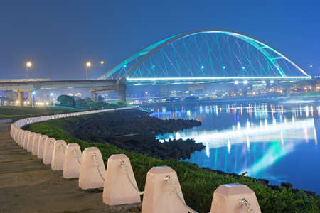 City night scene with illuminated bridge over river in Taipei, Taiwan, Asia. The bridge was named MacArthur Bridge No. 2. photo