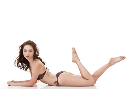 korean fashion: Sexy bikini woman of Asian lying down, full length portrait isolated on white background.