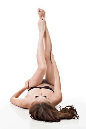 Young Asian woman lying with bare legs against studio white background. photo