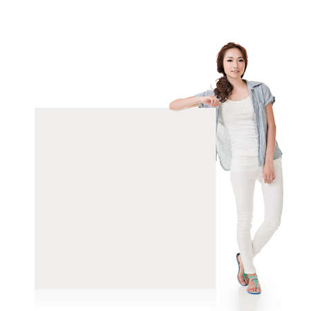 Attractive Asian woman lean on blank board of advertisement on white background. Stock Photo
