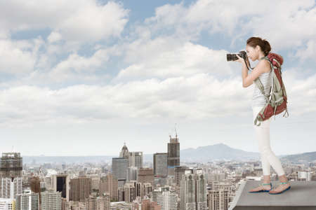 Asian young woman with professional camera photographing the city from the top. photo