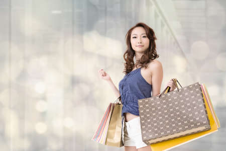 Modern woman shopping in mall holding bags. photo
