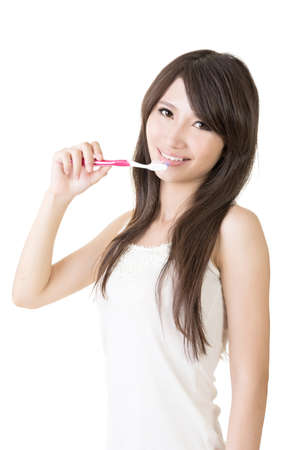 Attractive asian woman brushing teeth on the white background. photo