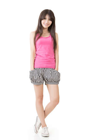 white singlet: Young casual pretty asian woman in pink singlet ans striped shorts. Isolated on the white background. Stock Photo