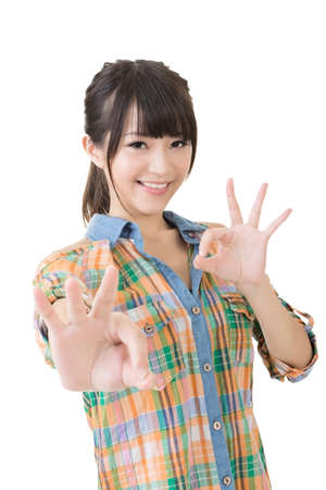 hand gestures: Young pretty asian woman showing OK sign with two hands. Close up portrait. Isolated on the white background. Stock Photo