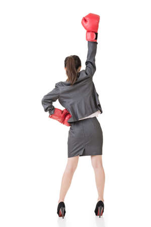 Young attractive asian business woman with boxing gloves are ready for battle. Rear view. Isolated on the white background. photo