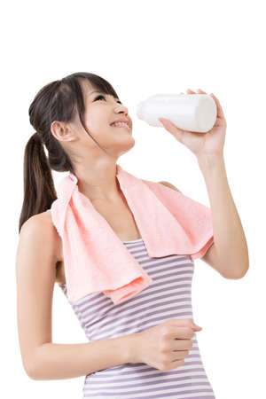 Sporty asian woman drinking water from a bottle after training. Closeup portrait on the white background. photo