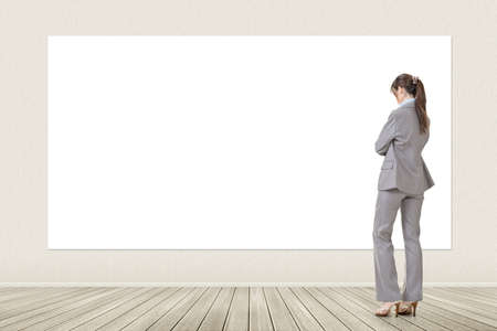 Asian elegant business woman standing and looking at blank white banner, board, placard or poster. Copy-space for advertise. photo