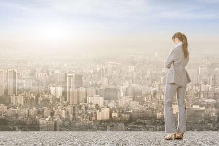 mujer mirando el horizonte: Empresaria asiática de pie en el techo y mirando a la ciudad, con el amanecer o el atardecer.