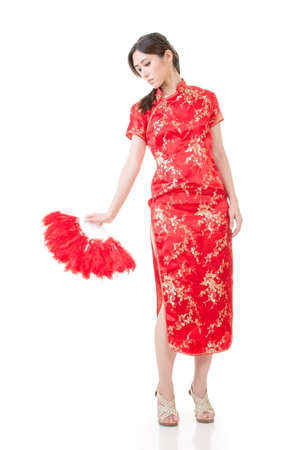 Young beautiful asian young woman with red fan in cheongsam (traditional clothing). Full length portrasit. Isolated on the white background. photo