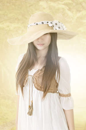 Young beautiful asian woman with knitted hat and long hair on the nature background. photo