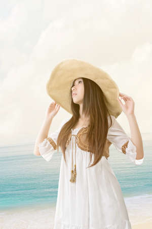 Outdoor portrait of a beautiful asian young woman wearing knitted hat at the beach with seascape background. photo