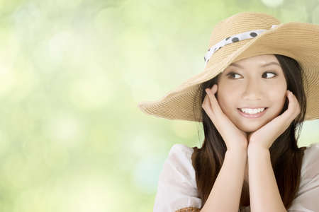 Closeup portrait of beautiful smiling asian girl, with knitted hat, against spring green bokeh background.