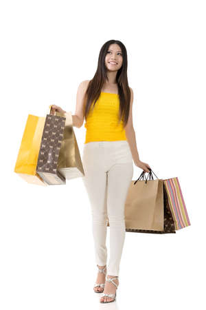 Attractive asian woman holding shopping bags and walking in studio. Full length portrait. Isolated on the white background. photo
