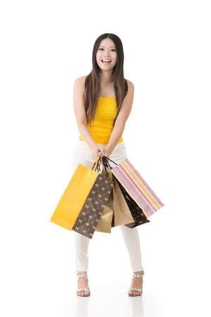 Attractive asian woman holding shopping bags and posing in studio. Full length portrait. Isolated on the white background. photo