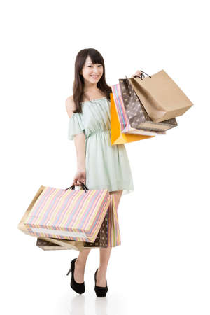 Attractive asian woman holding shopping bags. Full length. Portrait isolated on the white background. photo