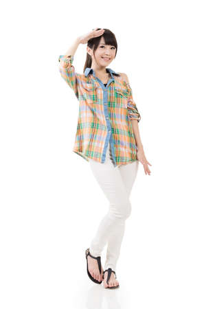 forehead: Young pretty casual asian woman looking ahead, away. Full length portrait. Isolated on the white background. Stock Photo