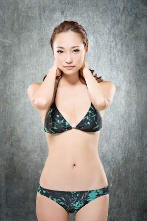 korean fashion: Attractive sexy asian lady in bikini. Close-up portrait. On the grunged background.