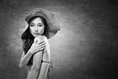 Attractive sexy asian lady in bikini with hat. Black and white photo. photo