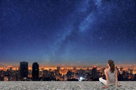 아시아 여자는 다시 카메라에, 지붕에 앉아, 별이 빛나는 하늘 아래 밤 도시에서 찾고.