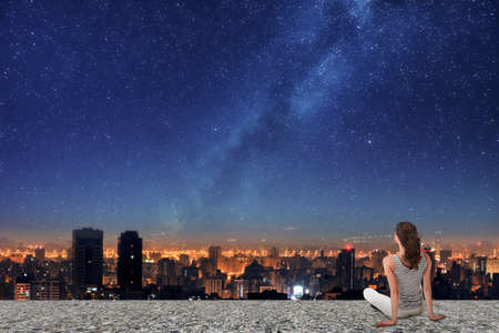 night sky and stars: Asian woman sitting on roof, back to camera, and looking on the night city under starry sky. Stock Photo