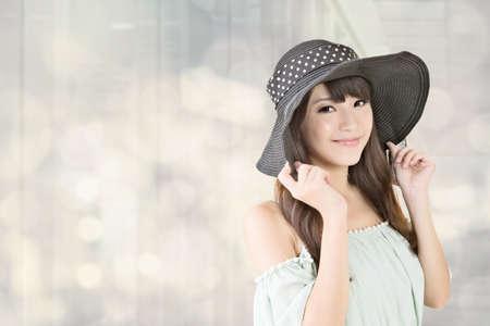 Jonge elegante Aziatische vrouw met zwarte hoed poseren tegen de achtergrond bokeh.