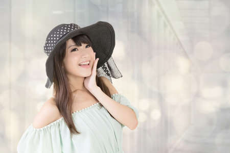 Young elegant asian woman with black hat posing against bokeh background. photo