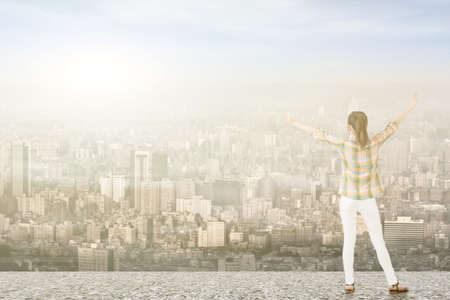 stretched: Young asian woman standing on the roof with stretched arms looking at the city.