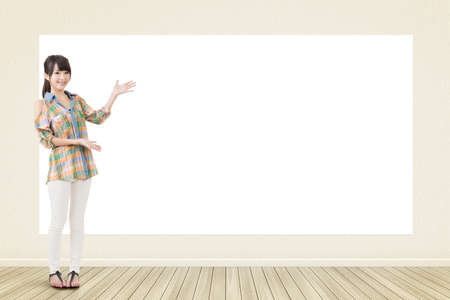 Asian casual smiling woman standing and showing blank white banner, board, placard or poster. Copy-space for advertise. 版權商用圖片