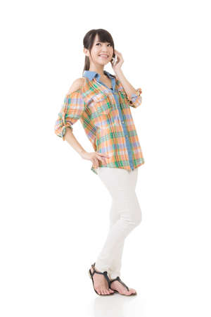 Young pretty asian woman standing and talking mobile phone. Full length portrait. Isolated on the white background. photo