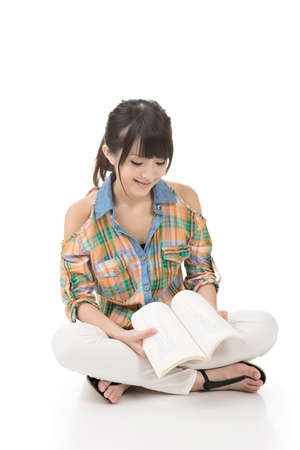 sitting on the ground: Young asian woman sitting on the ground and reading a book. Portrait isolated on white background.