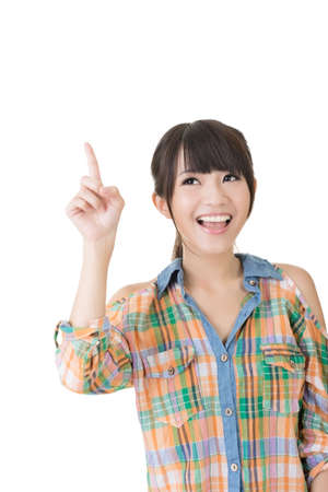 half  length: Young pretty asian woman pointing up. Half length portrait. Isolated on the white background.