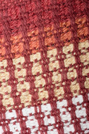 Red, beige and white knitted wool close-up photo