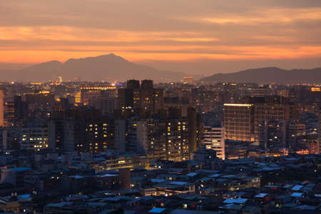 Sunset cityscape with dramatic clouds in orange and yellow color in Taipei, Taiwan, Asia. photo