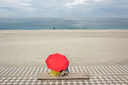Couple sitting on beach under red umbrella. Shot at famous attraction, Qixingtan Beach in Hualien, Taiwan, Asia. photo