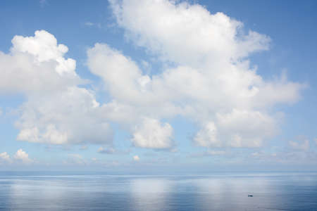 White fluffy clouds blue sky above a surface of the sea photo