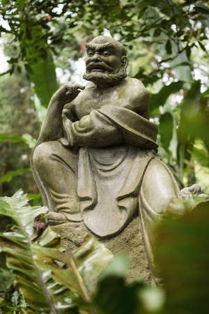 Old ruined Arhat Kanakbharadvaja statue in forest, Taiwan, Asia. photo