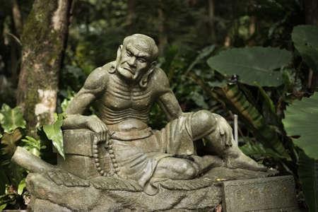 nirvana: Old ruined Arhat Kanakbharadvaja statue in forest, Taiwan, Asia.