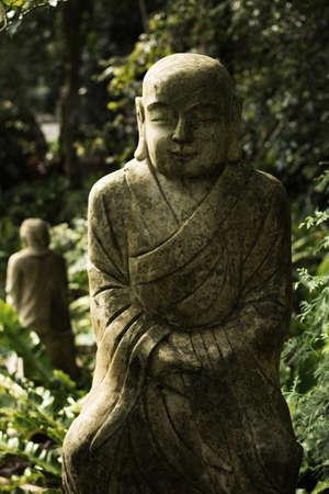 Ruined stone statue Ksitigarbha Bodhisattva in garden. photo