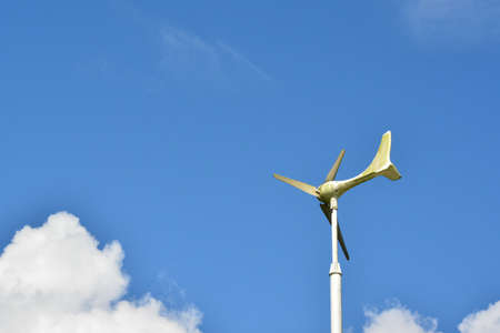 Windmill or weather vane against blue sky. photo