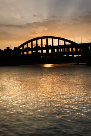 Sunset cityscape with silhouette of bridge under golden dramatic sky in Taipei, Taiwan, Asia. photo