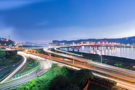 Night scene of cars light at highway and interchange in famous Guandu Bridge, Taipei, Taiwan, Asia. photo