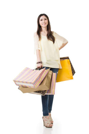 Happy smiling Asian woman hold shopping bags, full length portrait isolated on white . photo