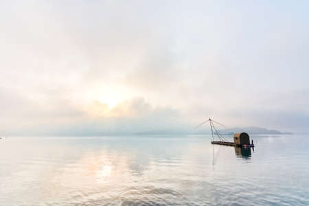 Landscape of famous Sun Moon Lake in the morning with a boat and mist in Taiwan, Asia. Stock Photo - 23723911