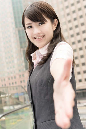 Business woman shake hand with you, closeup portrait in city. photo