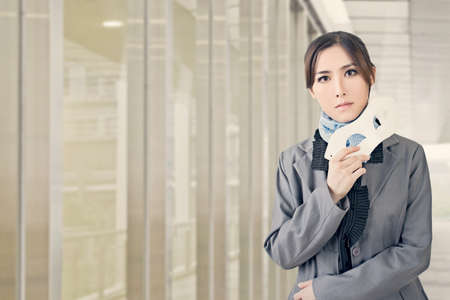 cheat: Asian business woman hold a mask and look at you, closeup portrait at modern office with copyspace.