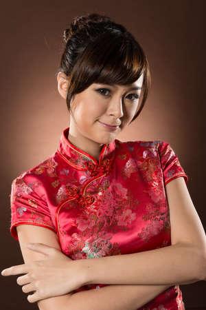 qipao: Attractive Chinese woman dress traditional cheongsam at New Year, closeup studio shot.