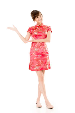 chinese woman: Smiling Chinese woman dress traditional cheongsam and introduce on white background. Stock Photo
