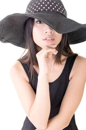 Aantrekkelijke elegante Aziatische jonge vrouw met bedekt halve gezicht van zwarte hoed. Close-up portret. Geïsoleerd op de witte achtergrond.